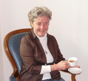 B. Seeholzer mit einer Teetasse in der Hand auf einem Stuhl sitzend